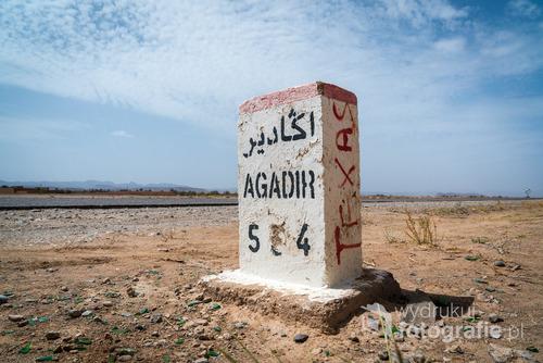 Znak przy drodze informujący o odległości do miasta Agadir. Maroko, sierpień 2016.