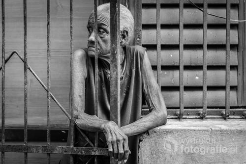 Kubańczycy spędzają większość swojego życia za kratami swoich domów, chroniąc się przed światem zewnętrznym. Havana, 2016.  Zdjęcie wyróżnione przez edytorów międzynarodowego konkursu fotograficznego LensCulture Portrait Awards 2017.