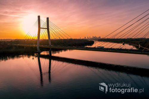 Zachód Słońca nad Warszawą oglądany poprzez przęsła mostu Siekierkowskiego
