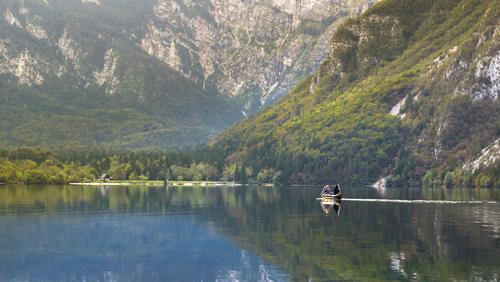 Para przemierzająca jezioro Bohinjsko w kajaku po równej jak stół tafli wody otoczona górami. Widząc to zazdrościłem im pomysłu ale w zamian za to, chociaż uchwyciłem ten moment na fotografii.