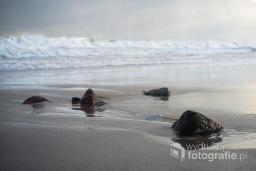 Zdjęcie wykonałem następnego dnia po tym jak fale sztormu na początku 2019 roku przykryły całą plażę. Morze wciąż huczało, ale przynajmniej pozwoliło sobie podejść do jego brzegu. Choć tylko na chwilę, bo zaczęła się zabawa w kotka i myszkę z wodą, która chciała złapać moje nogi, mimo, że parę sekund wcześniej przede mną uciekała.