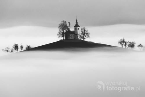Kościół pw. św. Tomasza w Słowenii wynurzający się z porannej mgły.