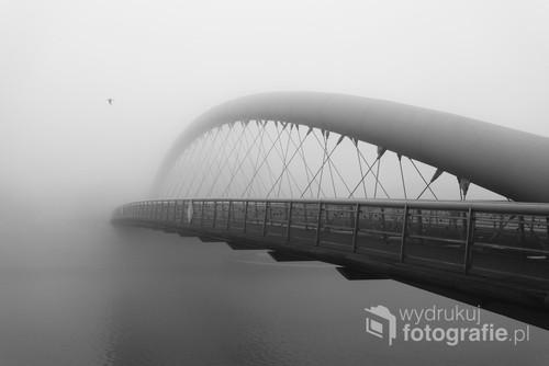 Kraków z kładką Ojca Bernatka, skąpany w porannej mgle.