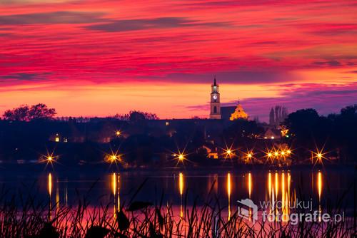 Nocny widoki na miasto z odbiciem w jeziorze Chodzieskim.