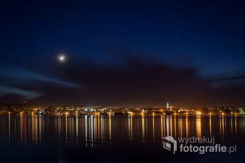 Nocna panorama z widokiem na miasto i jego odbiciem w jeziorze Chodzieskim.
