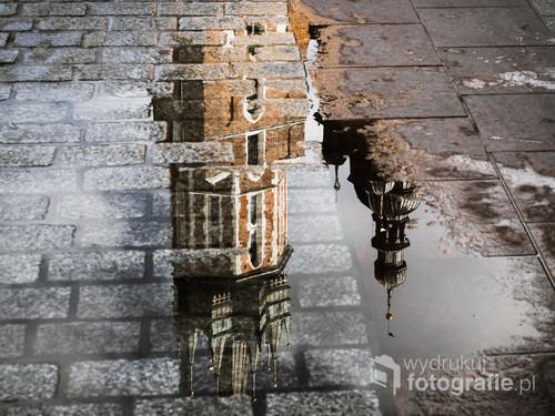 Fotografia wykonana została na Starym Mieście w Krakowie i przedstawia Kościół Mariacki odbity w kałuży przed Sukiennicami. Podczas, gdy wszyscy fotografowali patrząc w górę, ja spojrzałem na opak. Zdjęcie zostało nagrodzone wyróżnieniem w międzynarodowym konkursie