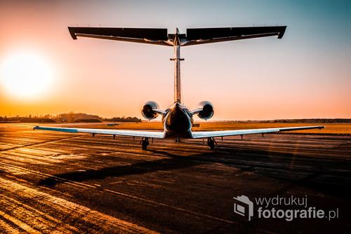 Fotografia przedstawia mały samolot pasażerski Embraer Phenom 100. Została zrobiona na lotnisku Katowice-Pyrzowice o zachodzie słońca.
