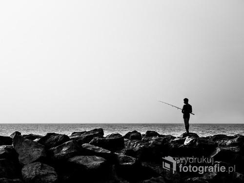Fotografia wędkarza została wykonana na plaży Sri Lanki niedaleko miejscowości Negombo nad Oceanem Indyjskim. Urzekła mnie w niej przestrzeń i proporcje człowieka w stosunku do głazów na brzegu.