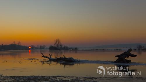 Fotografia powstała wczesnym, zimowym rankiem nad rzeką Narew. To dryfujące drzewo o wschodzie słońca było niesamowitą inspiracją. Nie było łatwo podejść do tego ujęcia gdyż lód przy brzegu jeszcze był zbyt cienki co wiązało się ze sporym ryzykiem nie tylko zmoczenia się przy temperaturze -18st C.
