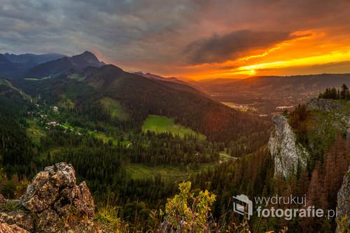 Fotografia została wykonana na Nosalu w Tatrach. Obraz przedstawia zachodzące słońce nad Miastem Zakopane. Ostatnie promienie słońca oświetlają ciepłym kolorem Giewont, który jest widoczny w lewej górnej części obrazu. Na Pierwszym Planie droga do Kuźnic tuż za nią pod Giewontem dostrzec można również Polane Kalatówki. Na zdjęciu widoczne są również - Gubałówka, Kolejka na Kasprowy Wierch, Polana Szymoszkowa, Krokiew...