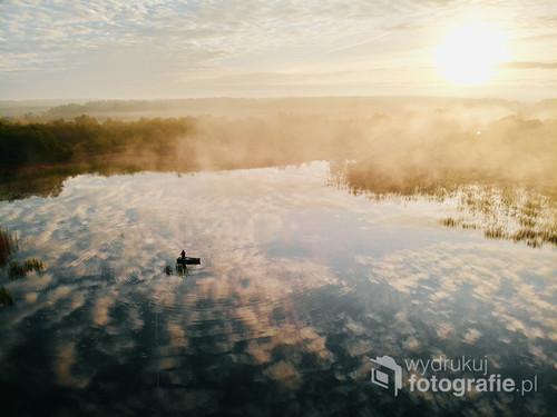 Samotny wędkarz na łodzi na jeziorze Orle pod Wejherowem. Zdjęcie wykonane z drona krótko po wschodzie słońca w październiku 2018. Wędkarz pojawił się zupełnie przypadkiem. Pozował nieświadomie.