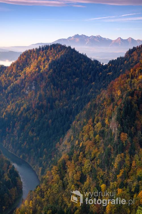 Fotografia została wykonana w jesienny poranek ze szczytu Czertezik i przedstawia przełom Dunajca wraz z widokiem na Tatry.