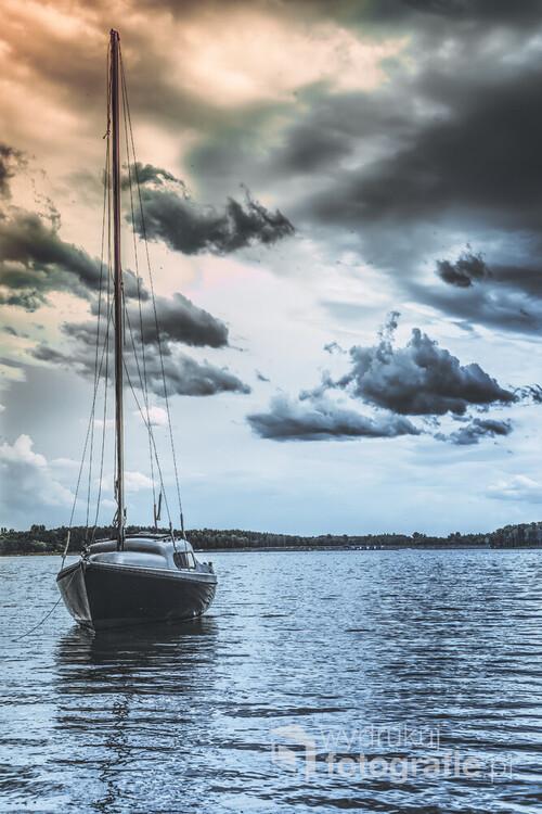 Lekko abstrakcyjne, popołudniowej ujęcie samotnie zacumowanej przy brzegu łodzi.