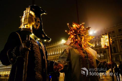 W niecodziennej scenerii Wenecji występują też szczególni aktorzy... Ich czasem jest karnawał. Pojawiają się wówczas zamaskowane postaci, których kostiumy skrywają często gości z odległych zakątków świata. Jest to prawdziwy festiwal wyobraźni. Obok tradycyjnych masek i strojów weneckich znajdujemy tu kunsztowne kostiumy historyczne, alegorie wszystkich pór roku, nocy i dnia, żywiołów lub najbardziej niezwykłe wytwory fantazji. Nie jest to karnawał muzyki i tańca, ale teatralności gestu i pozy. Jego uczestnicy istnieją po to, by być oglądanymi i oczywiście fotografowanymi przez licznie zgromadzonych z tej okazji turystów i zawodowych fotografów. Fakt, że występują w najdoskonalszej scenografii historycznego placu Świętego Marka, zmusza ich do szczególnej dbałości o to, jak się zaprezentują. Równocześnie uczestniczą w nieustającym konkursie na najpiękniejszy kostium, którego głównymi jurorami są nie odstępujący ich o krok fotografujący, a największym wyróżnieniem ilość zrobionych poszczególnym jego bohaterom zdjęć. I tak w mieście, które miastem nie jest, rokrocznie odbywa się karnawał nie będący karnawałem. Słońce wędruje do morza, zapalają się latarenki, rozświetlają witryny sklepów i kawiarni, kryształowe żyrandole prześwietlają okna pałaców wzdłuż Canal Grande. Mrok zatrzymuje mewy w locie. Pomiędzy jawą a snem przedstawienie trwa...