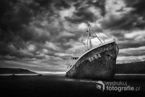Wrak starego kutra rybackiego wyrzuconego na brzeg oceanu. Wrak stanowi charakterystyczny punkt fotograficzny na Islandii.