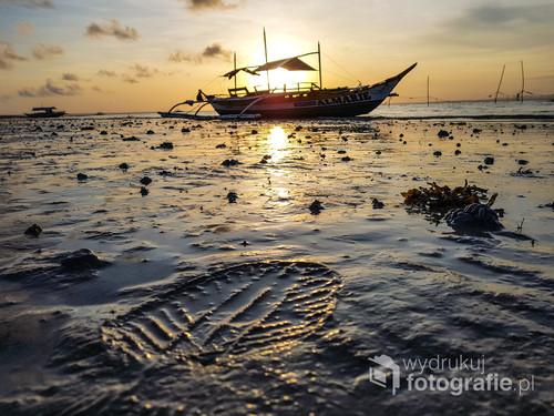 Wyspa Bantayan. Styczeń 2018.  Chciałem zostawić mój ślad na Filipińskiej ziemi… ale przetrwał tylko kilka minut. Tak naprawdę to jednak Filipiny odcisnęły we mnie głęboki ślad. Filipiny to biedny kraj szczęśliwych i pogodnych ludzi.  Przebywanie tutaj uczy życia tu i teraz. Obserwacja Filipińczyków była dobrą lekcją, jak docenić to, co mamy oraz bliskich, których mamy wokół siebie. Filipiny, jak większość krajów południowych uczą zwolnienia.  Oni mają czas – my podobno pieniądze.