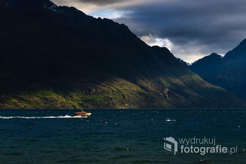Idealny moment dnia, za sprawą światła przebijającego się przez chmury powstała naturalna rama kadrująca łódź na jeziorze. Jeziora Wakatipu, Queenstown, Nowa Zelandia. 20-10-2018