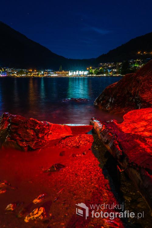 Długie naświetlanie oraz oświetlenie brzegu jeziora czerwonym światłem nadaje zdjęciu unikalnego charakteru. Queenstown, Nowa Zelandia. 22-10-2018