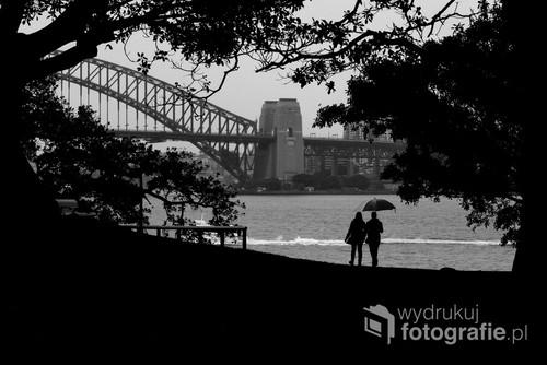 Para idąca brzegiem zatoki w Sydney, w tle Sydney Harbour Bridge. 10-10-2018