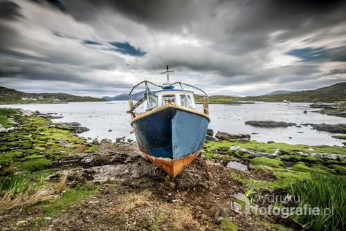 Zdjęcie przedstawia kadłub opuszczonej łodzi na wyspie Lewis znajdującej się w archipelagu Hebrydów Zewnętrzych administracyjnie należącego do Szkocji. Wyspa Lewis z racji swego dość surowego klimatu i krajobrazu słynie dziś z właśnie z tego, że na każdym kroku można znaleźć tam opuszczone domostwo, samóchód lub łódź. Ma to związek z masowym eksodusem ludoności z tych terenów w kierunku większych miast takich jak Edynburg, Glasgow lub Londyn.