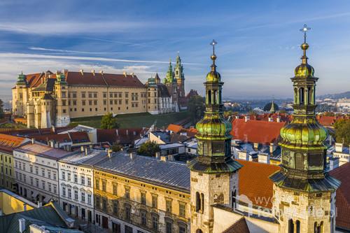 Poranny widok na Krakowskie Śródmieście. Na pierwszym planie wieże kościelne Kościoła św. Andrzeja, a w tle Wzgórze Wawelskie z Zamkiem Królewskim w otoczeniu okolicznych kamienic.