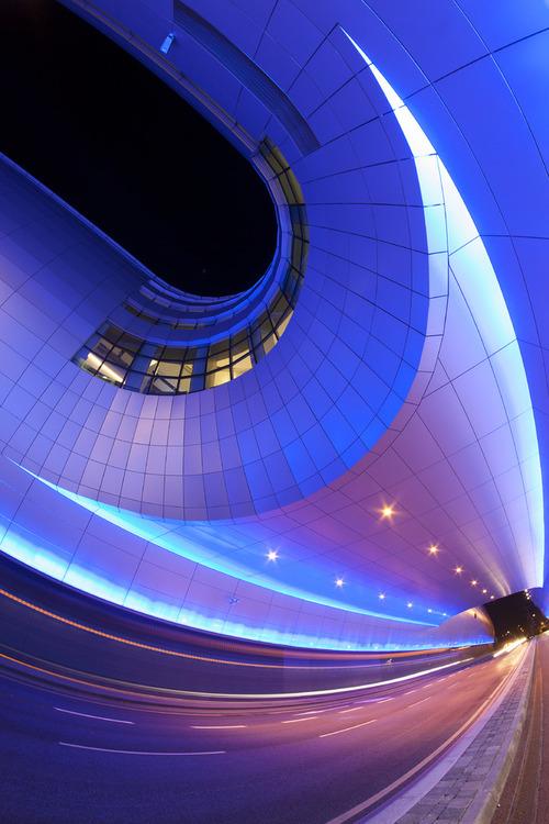 Fotografia przedstawia wspaniały, nowoczesny budynek międzynarodowego portu lotniczego w Dublinie, stolicy Irlandii. Jego kształt wzorowany jest na przekroju skrzydła samolotu. W dzień srebrne płyty lśnią odbijając światło słoneczne, wieczorem zaś iluminacje świetlne sprawiają iż nie da się przejść koło tego wspaniałego budynku obojętnie. Fotografia wykonana rybim okiem sprawia iż architektura staje się jeszcze bardziej futurystyczna i abstrakcyjna.