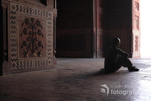 młody mężczyzna siedzący przy świątyni Taj Mahal - Indie