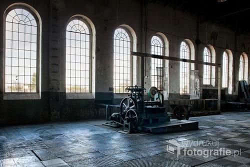 Zdjęcie nagrodzone w konkursie Ratujmy Zabytki Techniki organizowany przez Muzeum Walcownia Cynku w Katowicach. Na fotografii industrialne wnętrze fabryki i stara maszyna.