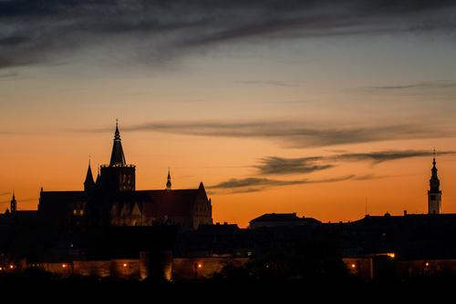 Zdjęcie przedstawia wieczorną panoramę Chełmna, zwanego Miastem Zakochanych i zostało wykonane obiektywem długoogniskowym, wraz z aparatem pełnoklatkowym. Wyraźnie zarysowuje się kontrast pomiędzy zbliżającym się momentem niebieskiej, a kończącym - złotej godziny. Dół kadru oświetlony zapalonymi chwilę wcześniej światłami miasta.