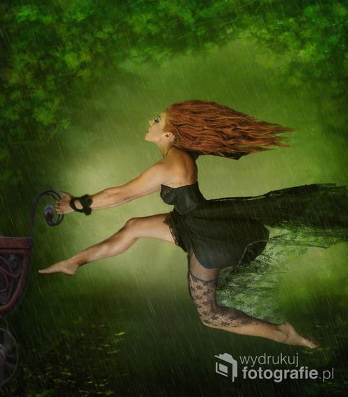 Zdjęcie przedstawia osobę zmagającą się z szarą codziennością. Zestawiono rudy kolor włosów z zielenią parku oraz dynamikę biegnącej osoby z padającym deszczem.