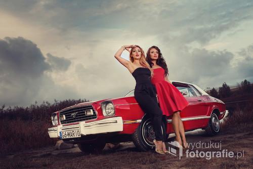 Zdjęcie przedstawia dwie młode kobiety, które przyjechały nad jezioro samochodem marki Ford Mustang.