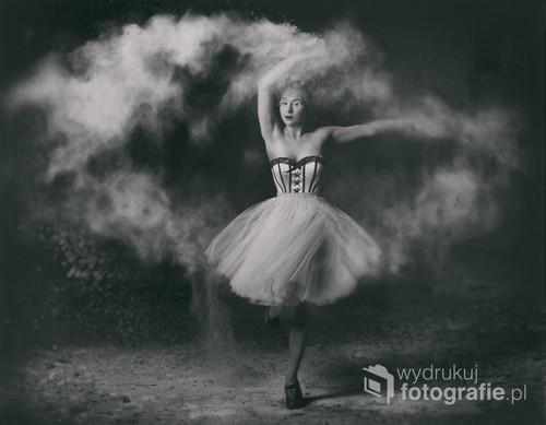 Zdjęcie przedstawia młodą kobietę podczas tańca w którym wykorzystano rozsypywaną mąkę.