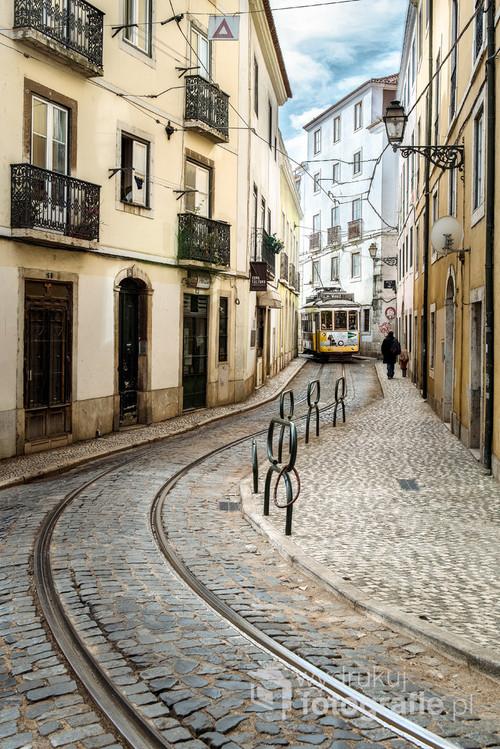 Linia tramwajowa nr 28 to wizytówka Lizbony. Prowadzi przez kręte i wąskie uliczki zabytkowej dzielnicy miasta. Przejażdżka takim tramwajem to emocjonujący sposób na zwiedzanie stolicy Portugalii. Chcąc uchwycić kadr, który jak najbardziej odda klimat tej trasy, musiałem poświęcić wiele minut na upolowanie tego właściwego momentu. Fotografia widoczna obok to finał tego planu i jednocześnie praca, która przywołuje cenne wspomnienia z podróży do Lizbony.