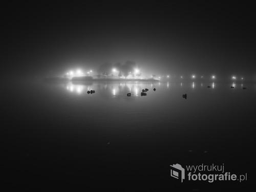 Rozświetlona wyspa, parku miejskiego w Suwałkach, nocą we mgle. Jesień.