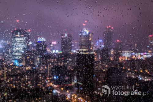 Widok na centrum Warszawy z wieżowca Warsaw Trade Tower w deszczową noc.