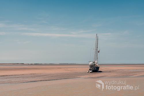 Łódź na mieliźnie podczas odpływu, Normandia, Francja.