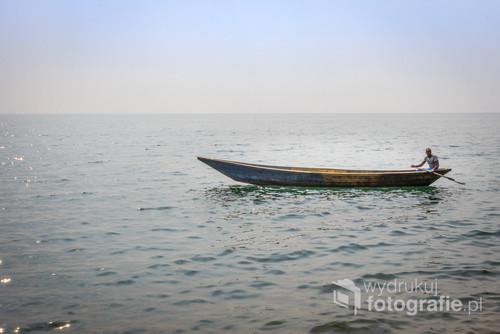 Jezioro Kivu należy do szlaku Wielkich Jezior Afrykańskich, w których skład wchodzi m.in Jezioro Wiktorii. Zdjęcie zostało zrobione w Rwandzie, niedaleko miasta Gisenyi. Na zdjęciu rybak wypływający po załadunek do pobliskiego, małego portu.