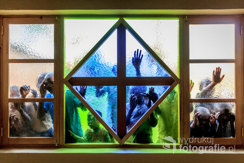 Zdjęcie wykonane w szkole w północnej Rwandzie. Dzieci, czekające na mnie na zewnątrz szkoły były ciekawe, co biały z aparatem robi w środku. Wtedy podeszły do szyby, aby się przyglądać - a ja wtedy zrobiłem to zdjęcie. Zdjęcie nagrodzone w konkursie fotograficznym HUMANDOC w kategorii Świat Różnorodnych Szerokości.