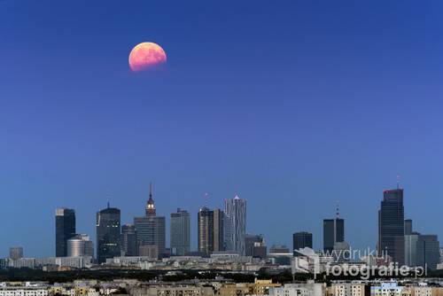 Full moon in partial eclipse over Warsaw city, Poland