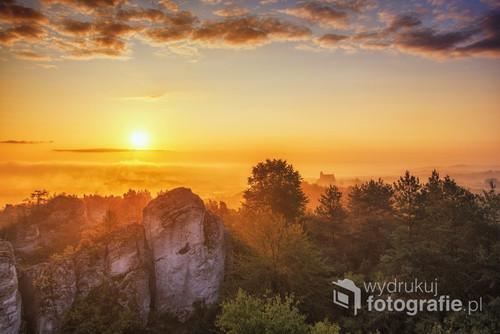 Powoli znad mgieł wyłaniające się słońce na skały mirowskie. W oddali zamek Bobolice.   Zdjęcie wykonane w czasie letniego festiwalu foto w hotelu Fajkier.  Jako jedyny z całej grupy udałem się na to miejsce.
