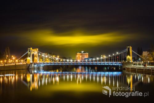 Nocna fotografia mostu Grunwaldzkiego i jego odbicia w wodzie