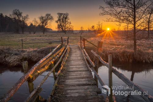 Drewniany mostek nad Jeziorką o zachodzie słońca