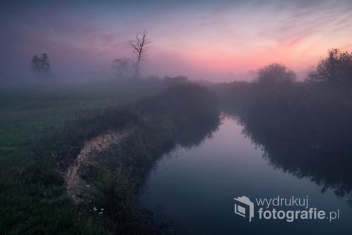 Świt nad rzeką w mglisty poranek