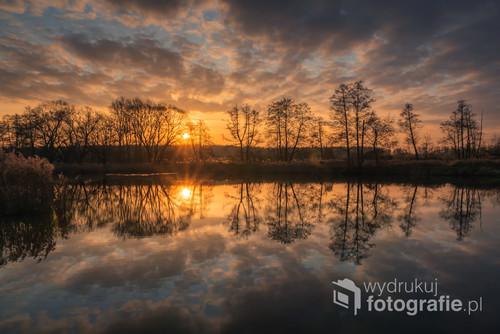 Wschód słońca nad stawem i jego odbicie w wodzie