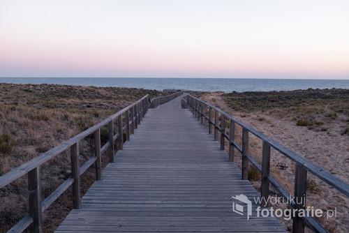 Fotografia przedstawia kładkę prowadzącą wprost do morza na południowym wybrzeżu Portugalii, w pobliżu miejscowości Armação de Pêra