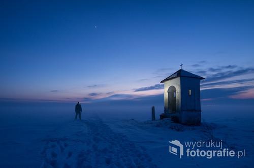 Kapliczka wśród pól, w mglisty zimowy wieczór. Miejscowość Wyszatyce, woj. podkarpackie.