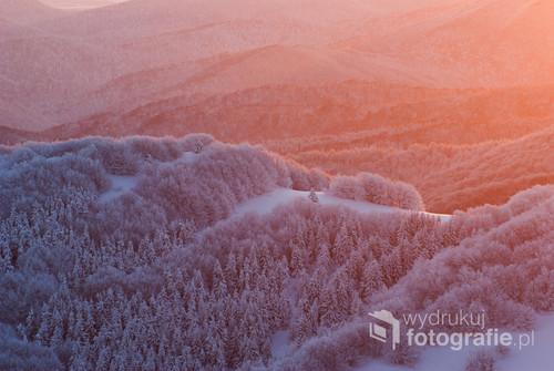 Zdjęcie wykonane w Bieszczadzkim Parku Narodowym. Pierwsze promienie wschodzącego słońca muskają stoki zalesionych wzgórz.