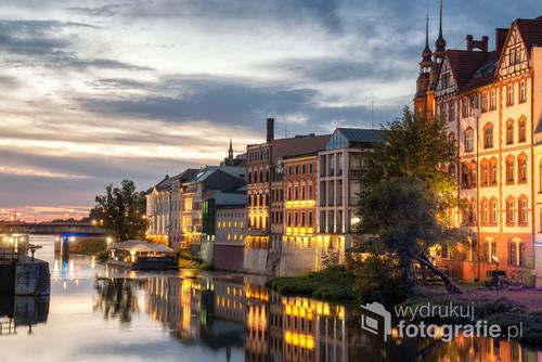 Opole to piękne śląskie miasto. Zdjęcie wykonane wczesnym wieczorem, przedstawia tzw. Opolską Wenecję, czyli zabytkowe budynki znajdujące się nad samym brzegiem kanału Młynówka.