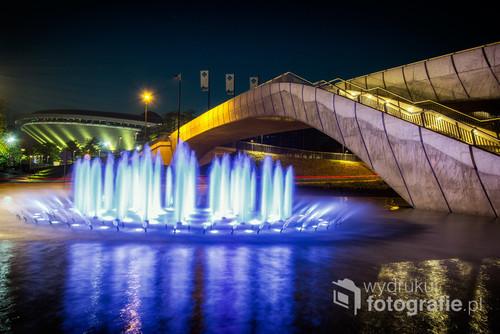 Kolorowa fontanna znajdująca się w sąsiedztwie siedziby Narodowej Orkiestry Symfonicznej Polskiego Radia i katowickiego Centrum Kongresowego. W tle widoczny Spodek - najbardziej znany obiekt tego miasta.