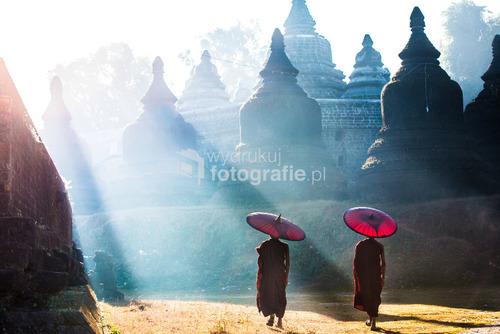 Młodzi mnisi przechadzający się wokół świątyni tuż po wschodzie słońca w starożytnym mieście Mrauk U, Birma 2016